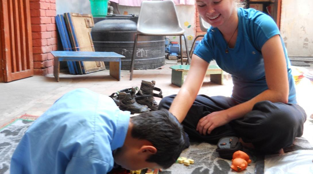 An intern from Projects Abroad playing with a child from a local nursery as part of her physiotherapy internship in Nepal.